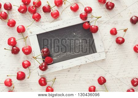 Fresh cherries around empty chalkboard.  Overhead view, blank space