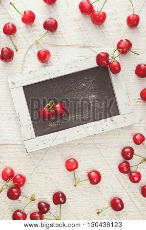 Red cherries scattered on rustic table and heart shaped pair of cherries on empty chalkboard. Overhead view, blank space