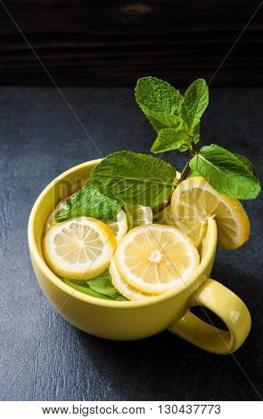 Cold lemonade. Detox cocktail. Refreshing homemade lemonade on stone table. Detox fruit infused flavored water. Refreshing summer drink