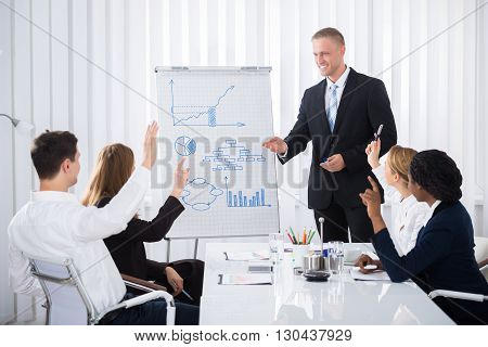 Group Of Businesspeople Raising Their Hands In Conference