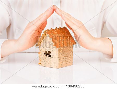 Female hands saving house of gold of color on the table