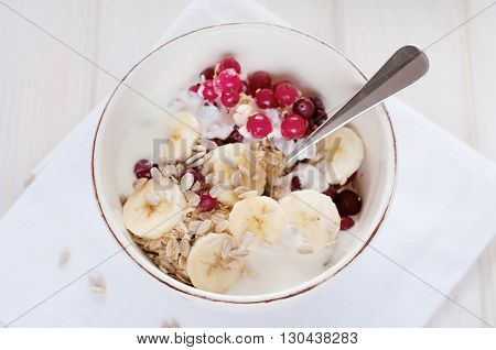 Healthy breakfast. Oatmeal with bananas cranberries sunflower seeds and yogurt.