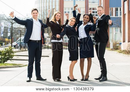 Group Of Happy Multi-racial Businesspeople Standing With Arm Raised In Front Building