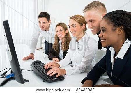 Team Of Businesspeople Looking At Computer In Office