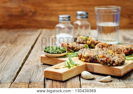 green lentils corn pepper fritters on dark wood background
