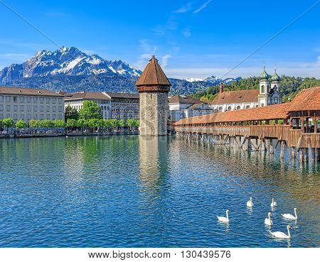 View on the Reuss river with the Water Tower and the Chapel Bridge in Lucerne, Switzerland, Mt. Pilatus in the background.