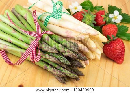 Fresh asparagus with strawberries on wood. Vegan food vegetarian and healthy cooking concept.