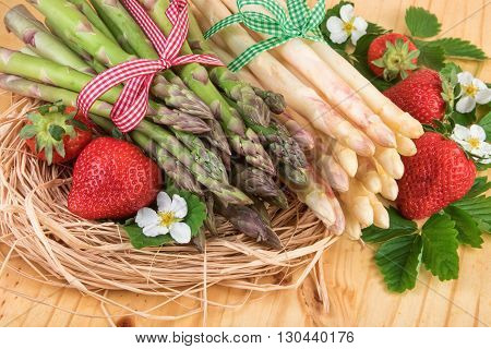 Green and white asparagus with ripe strawberries. Retro still life.