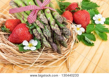 Green asparagus with fresh strawberry on woodem table. Closeup.