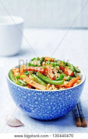 Millet carrots green beans Stir-Fry on a light background