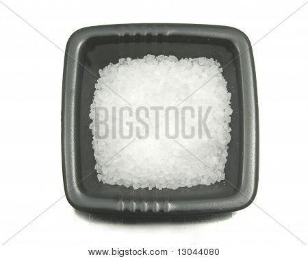 Black Bowl Of Chinaware With Salt On Reflecting Surface