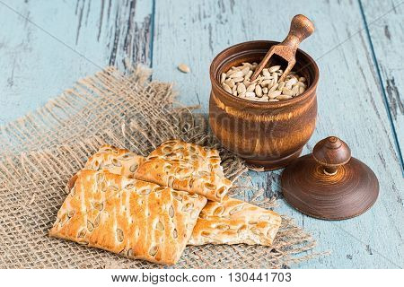 Peeled sunflower seeds in a wooden pot and cookies with sunflower seeds on a sacking on a blue background.