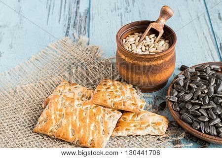 Sunflower seeds in a wooden crockery and cookies with sunflower seeds on a sacking on a blue wooden background.
