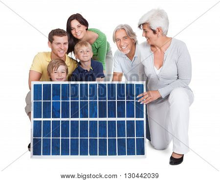 Portrait Of A Happy Family Holding Solar Panel Against White Background