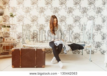 Girl sits on bed and collects clothes into a suitcase
