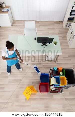 High Angle View Of Young Female Janitor Mopping Wooden Floor With Caution Sign