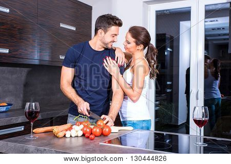 Beautiful young couple cooking while enjoying a glass of wine in the kitchen.