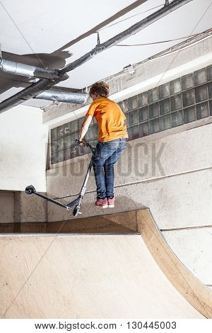 Boy Has Fun Riding His Scooter In The Skate Hall
