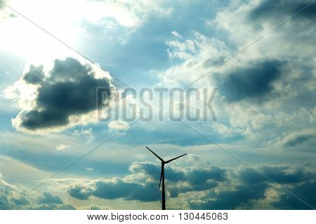 Wind turbine under a dramatic sky with strong clouds.