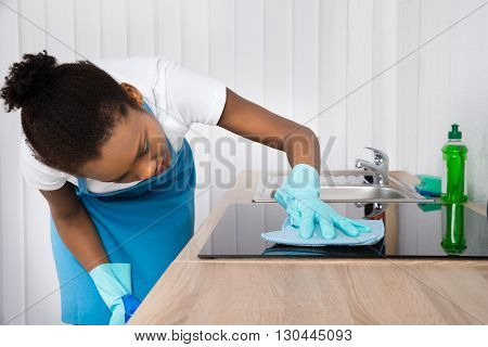 Young Happy Female Janitor Cleaning Induction Stove With Spray Bottle In Kitchen