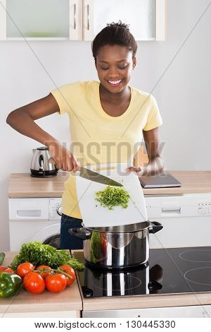 Happy Young African Woman Putting Chopped Vegetables In Utensil