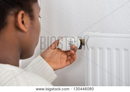 Woman Adjusting Temperature Of Radiator Using Thermostat