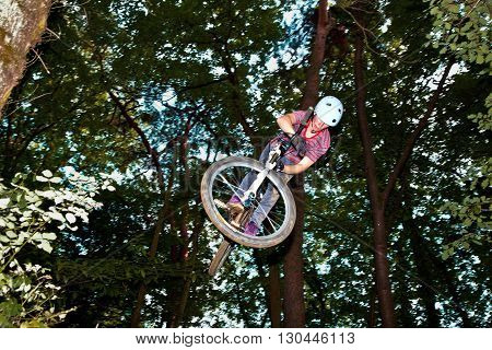 Cute Teen Jumping With His Bike Over A Natural Ramp In The Forest