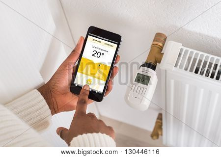 Close-up Of Woman's Hand Adjusting Temperature Of Thermostat Using Cellphone