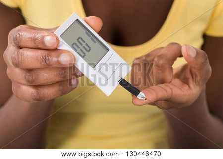 Close-up Of Young Woman Hand Using Glucometer To Check Blood Sugar Level