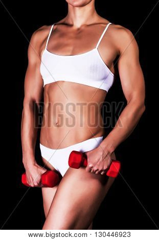 Sporty woman with red barbells, isolated on a black background