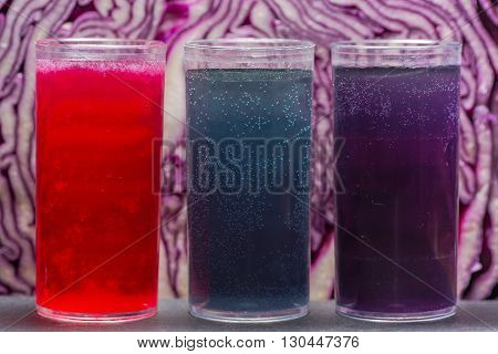 Red cabbage pH indicator solution. Acidic lemon juice (red) alkali sodium bicarbonate (blue) and neutral tap water (purple) showing property of anthocyanin in red cabbage juice