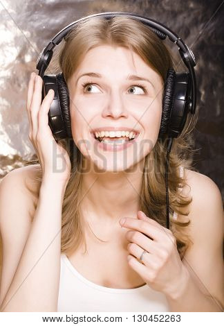 young pretty blond woman listening music and singing in big earphones close up, lifestyle people concept