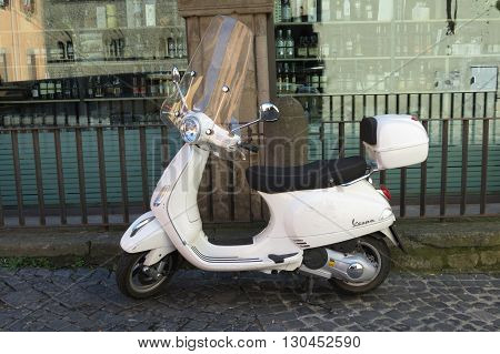 ROME ITALY - CIRCA OCTOBER 2015: off white Vespa motorbike parked in a street