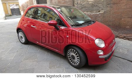SIENA ITALY - CIRCA APRIL 2016: red FIAT 500 car (new version) parked on a street in the city centre