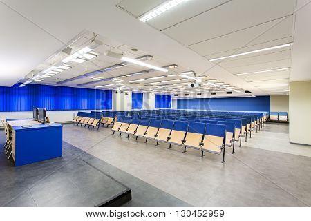Medium-sized blue lecture hall with desk platform