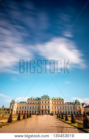 View on Upper Belvedere palace with alley in Belvedere historic building complex in Vienna. Long exposure technic with blurred clouds and blurred people silhouettes