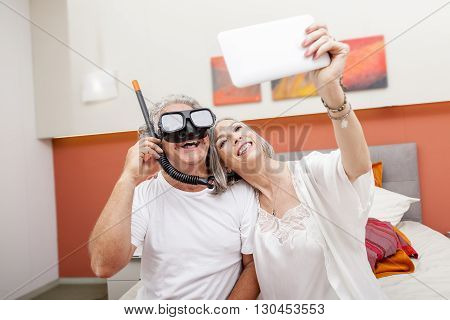 Mature Happy Couple Takes A Selfie Joking In Hotel Room