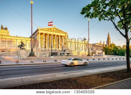 Austrian parliament building with Athena statue on the front in Vienna on the sunrise. Long exposure image technic with burred car