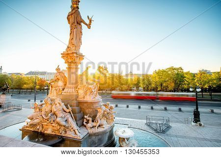 Athena statue near Parlament building with Vienna cityscape and old tram on the background on the sunrise