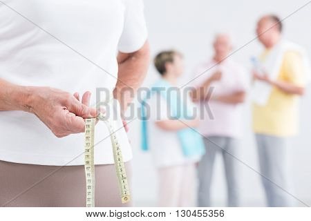 Close-up of an old lady at a health club holding a measure tape in her waist with her friends in the blurred background