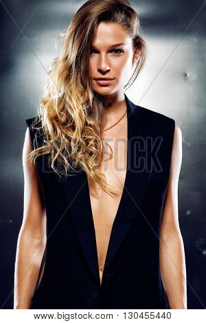 Sexy model in the black vest on grey background