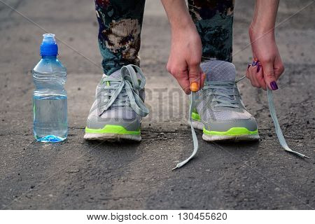 girl stopped running to tie the laces on running shoes. fitness girl training outdoors.