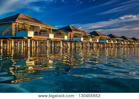 Beautiful water villas on the vibrant blue tropical sea during sunset