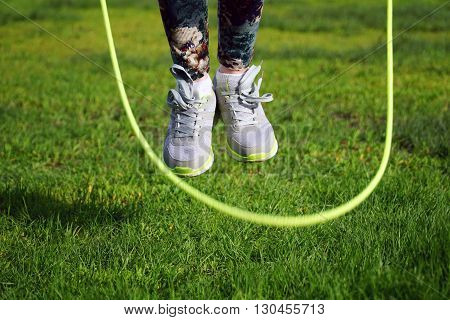woman jumping on a skipping rope in a park close-up.