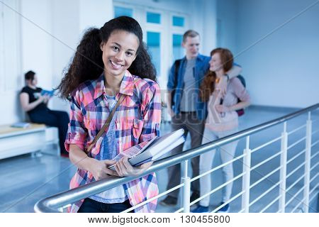 Cheerful high school student in school hallway before lecture
