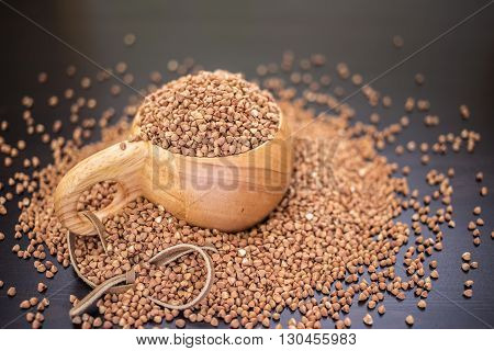 buckwheat groats in the wooden mug and scattered on black table