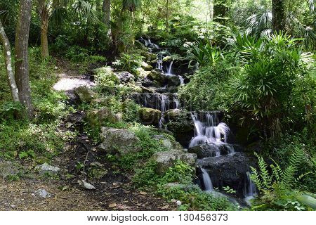Waterfall flowing down moss covered rocks along green foliage at a State Park in Florida in the Springtime.