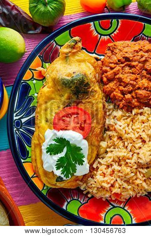 Chili relleno chili peppers filled with cheese in dish with with rice and frijoles beans