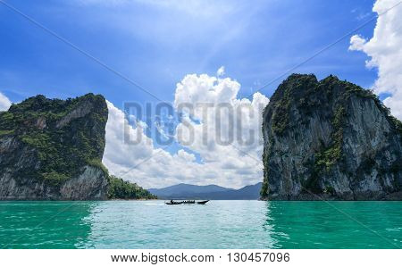 Boat traveling pass canyon mountains on a great lake in Thailand
