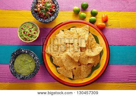 Nachos tortilla chips with mexican sauces on colorful table